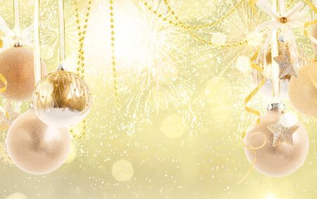 Hanging golden christmas balls on golden bokeh background with copy space