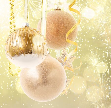 Hanging golden christmas balls on golden bokeh background close up Stock Photo