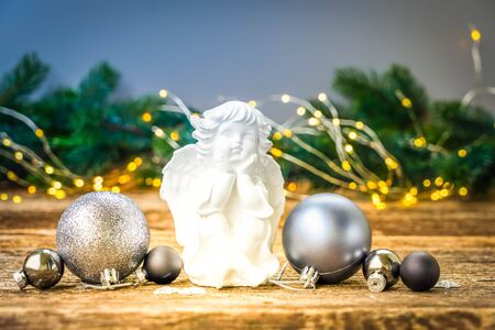 Christmas angel with silver decorations on natural wooden table, toned
