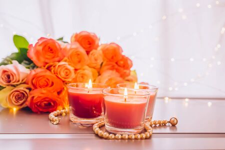 Glowing candles with rose fresh flowers bouquet on gray table, close up home interior details, toned