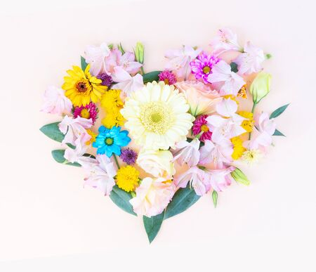 Flowers composition in the shape of heart made of eustoma and daisy flowers on pink background. Flat lay, top view scene. Stock Photo