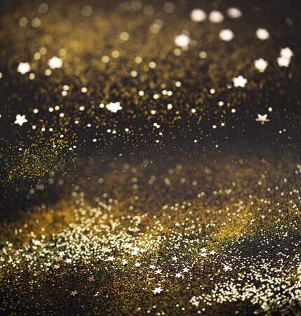 Beautiful Christmas light background. Abstract glitter bokeh and scattered sparkles in gold, on black square background