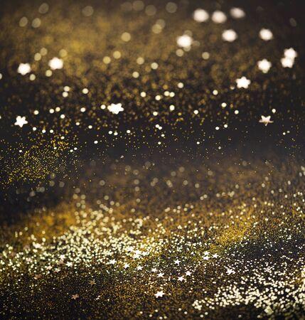 Schöner Weihnachtslichthintergrund. Abstraktes Glitzer-Bokeh und verstreute Funken in Gold, auf schwarzem quadratischem Hintergrund