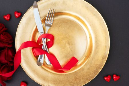 Served table for Valentines Dinner, golden plate and cutlery, top view
