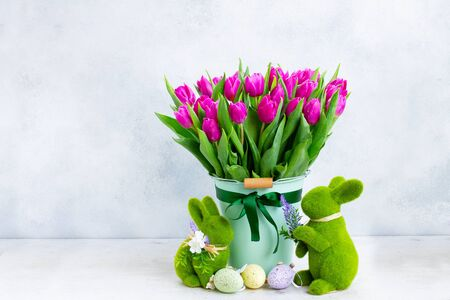 Purple fresh tulip flowers in pot with easter bunny on gray background with copy space Zdjęcie Seryjne