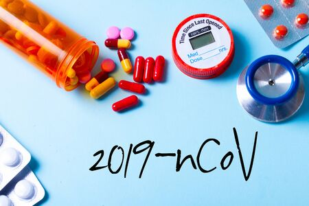 Healthcare concept - pills and medical stethoscope on blue background, new coronavirus concept