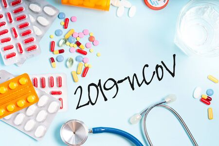 Colorful pills with glass of clear water over blue background, top view Medical pharmacy and new 2019 ncov virus concept