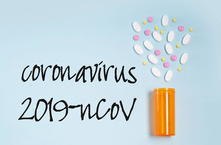 New virus concept - orange bottle with scattered pills on blue background with copy space Stock Photo
