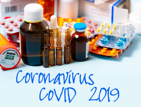 Coloful pills with glass of clear water over blue background with copy space. covid 2019 virus concept