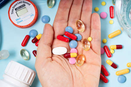 Someones hand holding colorful pills with glass of clear water over blue background. Medical pharmacy concept.