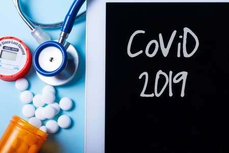 Pile of medical pills with tablet screen on blue background, coronavirus covid 2019 concept