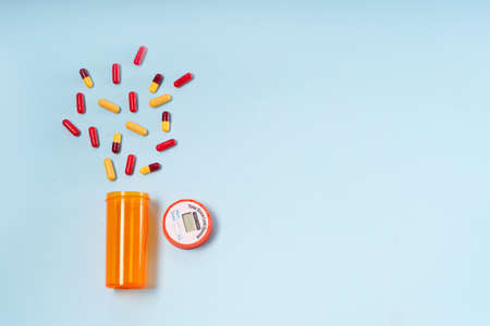 Healthcare concept - orange bottle with scattered pills on blue background with copy space