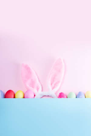 Easter rabbit flaffy ears and colored easter colored eggs, top view flat lay on pink and blue plain minimal background with copy space Banque d'images