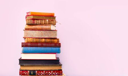 Pile of books on blue wooden shelf, copy space on pink wall background Zdjęcie Seryjne