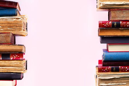 Rows of old antique books on pink background with copy space