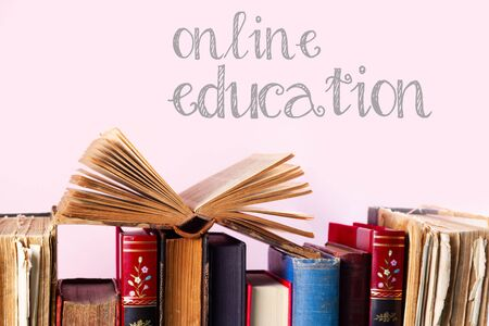 Pile of old books on pink background, online education concept