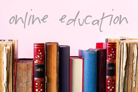Row of old books on wooden shelf on pink background, online education concept