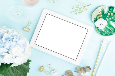 Creative wedding composition with metalic photo frame mock up, flowers on blue desk background. Flat lay, top view stylish art concept.