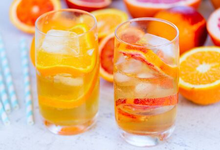 Summer refreshing cold citrus drinks in glasses with ice on white table
