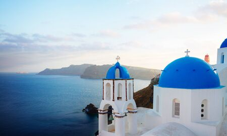 traditional greek village Oia of Santorini, with blue domes of churches in sunset light, Greece, panorama Standard-Bild