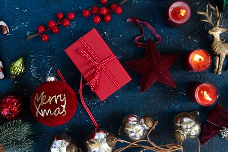 Christmas flat lay scene with gift boxes and festive decorations, Christmas celebration and gift giving concept, copy space on classic blue background