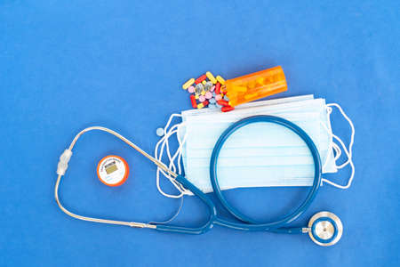 Healthcare concept - stethoscope, masks and pills on blue , corona viruses concept