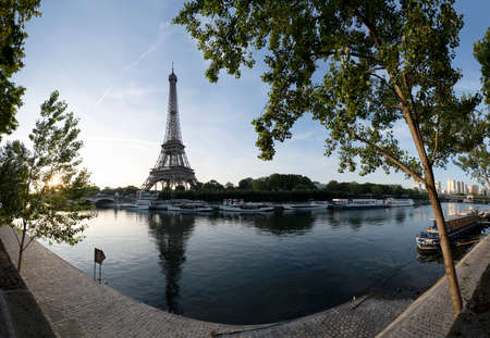 Paris Eiffel Tower and river Seine with sunrise sun in Paris, France. Eiffel Tower is one of the most iconic landmarks of Paris, panorama