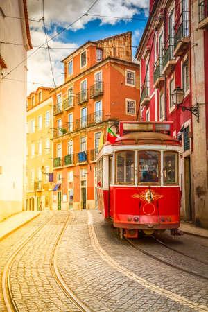 tram on narrow street of Alfama, Lisbon, Portugal with sunshine