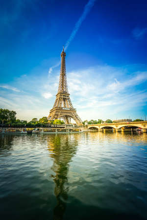 Paris Eiffel Tower reflecting in river Seine with bridge Pont dIena in Paris, France. Eiffel Tower is one of the most iconic landmarks of Paris with sunshine