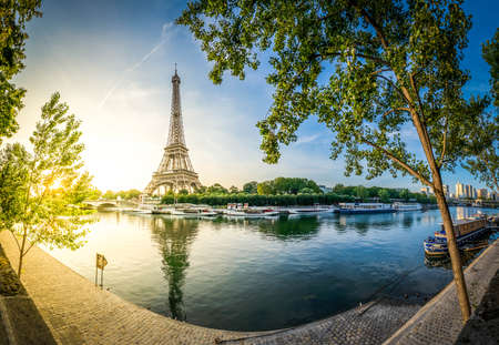 Paris Eiffel Tower and river Seine with sunrise sun in Paris, France. Eiffel Tower is one of the most iconic landmarks of Paris, panorama with sunshine
