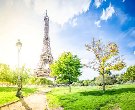 Paris Eiffel Tower with park in Paris, France. Eiffel Tower is one of the most iconic landmarks of Paris, with sunshine