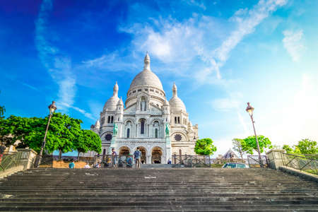 view of world famous Sacre Coeur church facade with stairs at summer, Paris, France with sunshine