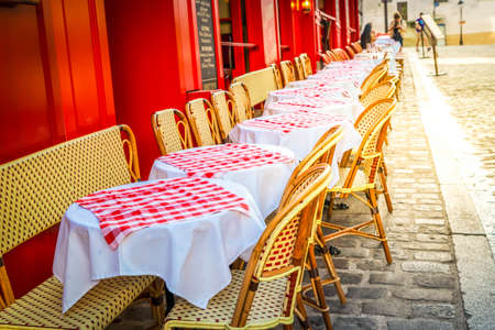 view of romantic Monmartre street with cafe tables close up, Paris, France, toned with sunshine Banque d'images