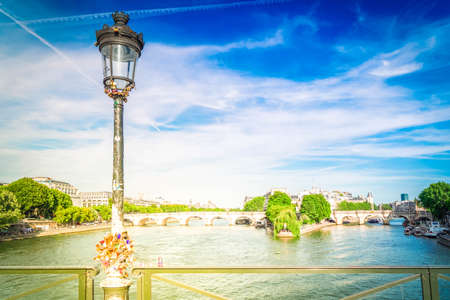 bridges Pont des Arts and Pont Neuf and Seine river with moored boats, Paris, France with sunshine