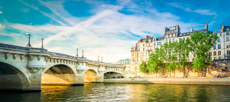 bridge Pont Neuf and Seine river with old houses, Paris, France, web banner format with sunshine