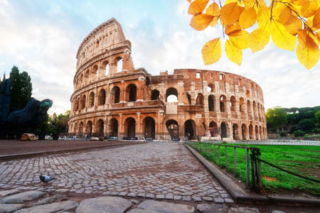 ruins of antique Colosseum with green grass lawn in sunise lights, Rome Italy at fall day Banque d'images
