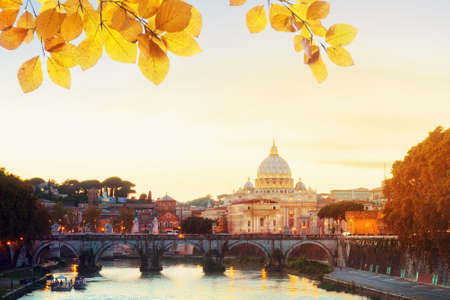 St. Peters cathedral over bridge and Tiber river in Rome at sunset, Italy at fall day