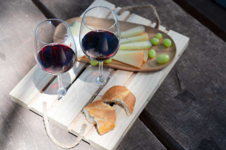 picnic with glasses of red wine, bread and cheese 免版税图像