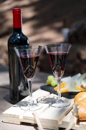picnic with red wine bottle and glasses, bread and cheese