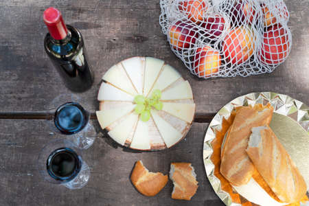 picnic with red wine, bread and cheese, top view