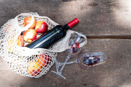 net shopping bag with red wine bottle and glasses, top view