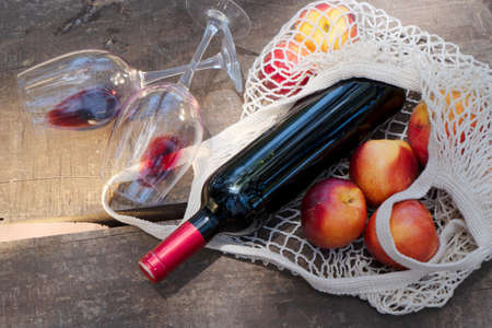 net shopping bag with red wine bottle and glasses