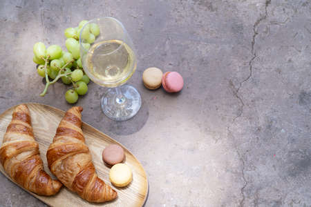 picnic with wine and croissants on concrete table
