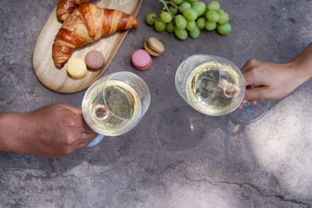 picnic with wine and croissants, couple cheers with glasses, top view