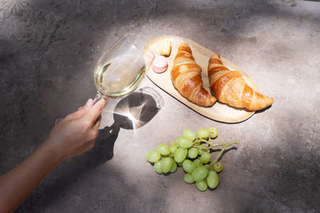picnic with white wine and croissants, someone hand holding glass