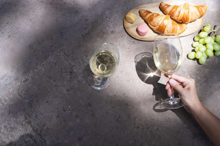 picnic with white wine and croissants, someone hand holding glass, copy space on the table 免版税图像
