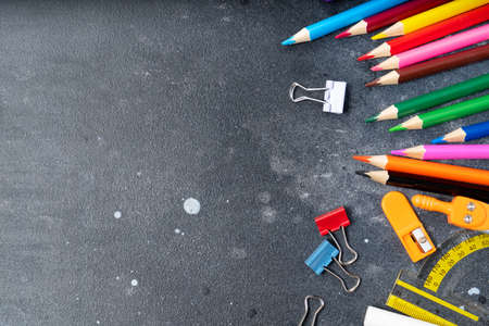 Back to school concept, border with colorful school supplies on blackboard background with copy space, top view scene