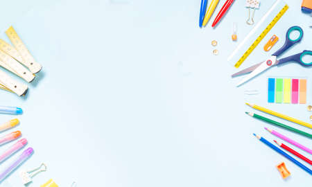 Back to school concept with colorful school supplies border on blue background with copy space, top view, web banner format
