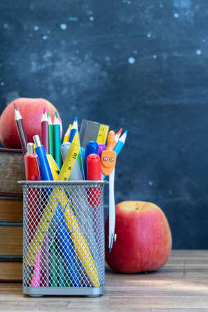 Back to school concept, school supplies with books and apples on blackboard background with copy space Фото со стока