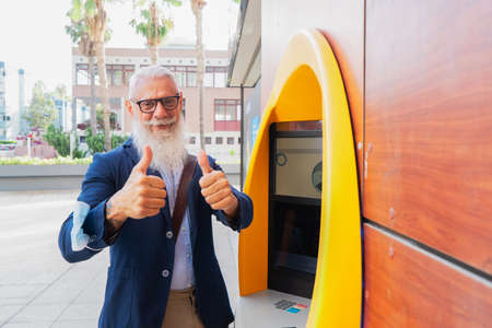 Senior man with ATM, happy smiling mature male with bank cash machine - Concept of business, banking account and lifestyle people Stock fotó